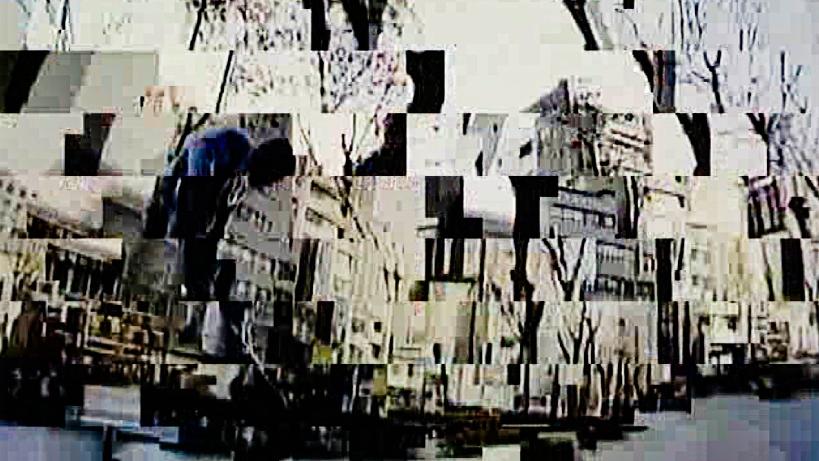 A video still is broken up into a mosaic, with what could be a person hunched over in the left-hand side of the screen. The broken-up background is composed of buildings and trees.