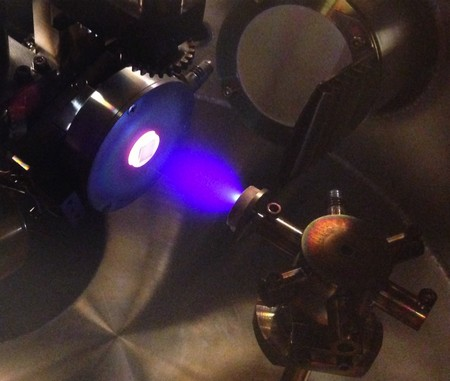 Inside view of vacuum chamber in which the process of 'pulsed laser deposition' takes place, used to create the hafnium oxide crystals in this study. On the left the glowing substrate on which the film is growing with atomic control; in the center the blue plasma of ions that is created by shooting a laser on a target with the right chemical composition (target visible on the right side of the figure). | Photo Henk Bonder, University of Groningen