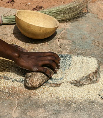 An african woman grinding cereals millet into flour using traditional grindstones, Burkina Faso.